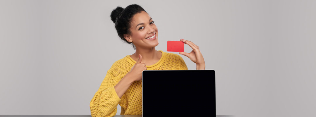 woman smiling while holding card